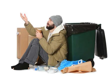 Poor homeless man sitting near trash bin isolated on white