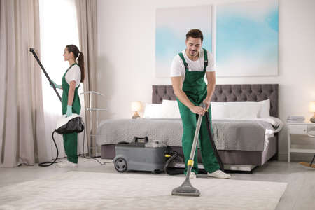 Team of janitors cleaning bedroom with professional equipment