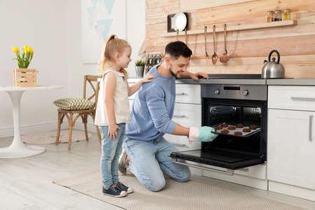 Padre con su hija para hornear galletas en el horno en casa
