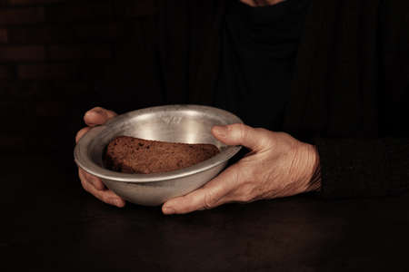 Poor mature woman holding bowl with bread at table, closeup