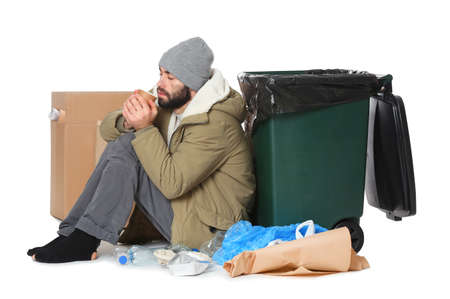 Poor homeless man sitting near trash bin isolated on white