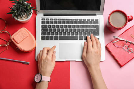 Blogger mit Laptop, Kaffee und verschiedenem Zubehör auf farbigem Hintergrund, Draufsicht Standard-Bild