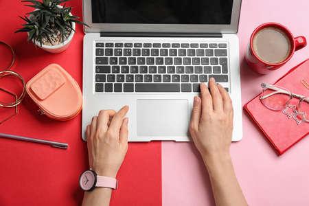 Blogueur avec ordinateur portable, café et différents accessoires sur fond de couleur, vue de dessus Banque d'images