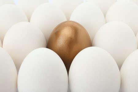 Huevo de oro entre los ordinarios como fondo, primer plano Foto de archivo