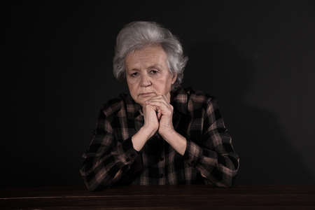 Poor upset woman sitting at table on dark background