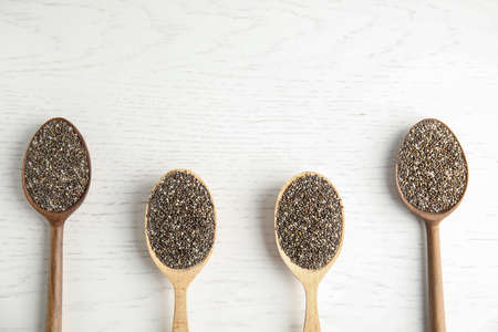 Spoons with chia seeds on wooden background, flat lay. Space for text Stockfoto