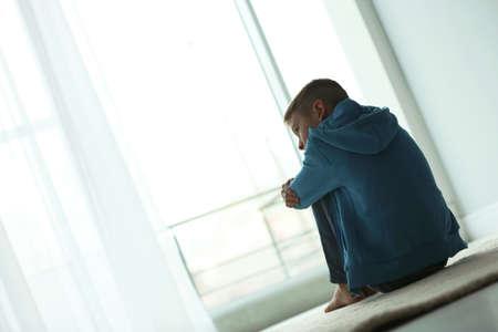 Zdenerwowany chłopiec siedzi w pobliżu okna w pomieszczeniu. Miejsce na tekst