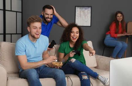 Amigos emocionales jugando videojuegos en casa Foto de archivo