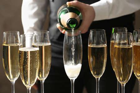 Camarero vertiendo champán en copa, vista de cerca