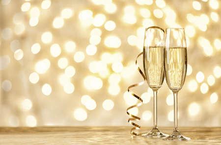 Copas de champán en la mesa contra luces borrosas. Espacio para texto