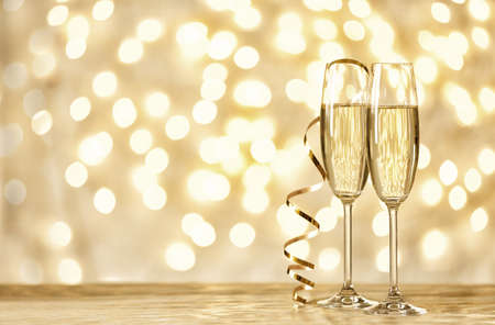 Glasses of champagne on table against blurred lights. Space for text