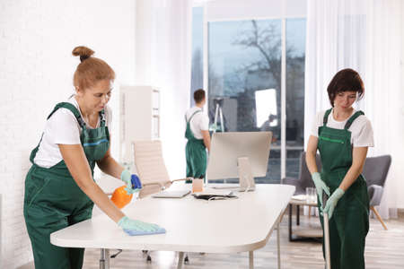 Team of professional janitors working in modern office. Cleaning service Zdjęcie Seryjne
