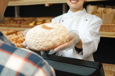 Baker giving customer fresh bread in store, closeup
