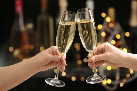 Persone che tintinnano bicchieri di champagne su sfondo sfocato, primo piano
