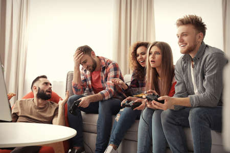 Emotional friends playing video games at home Stock fotó