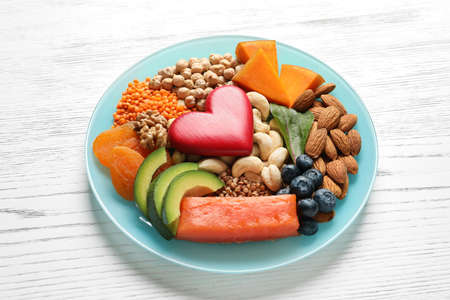Plate with heart-healthy products on wooden background