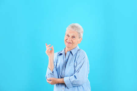 Portrait of grandmother in stylish clothes on color background 写真素材