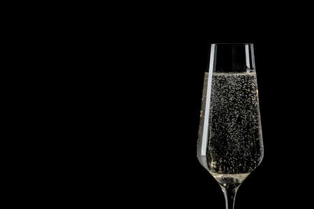 Glass of champagne on black background, space for text