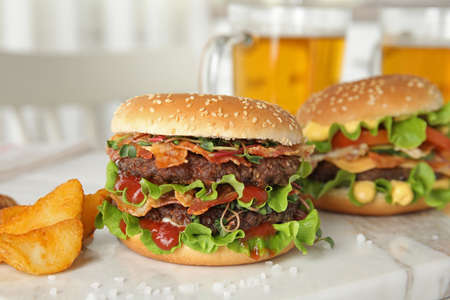 Tasty burgers with bacon and fried potatoes served on board Stockfoto