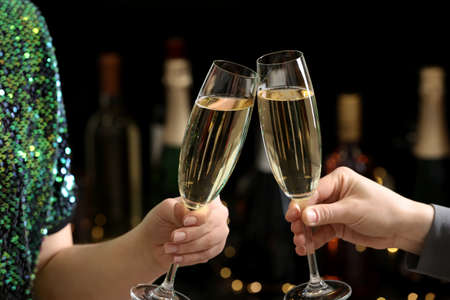 People clinking glasses of champagne on blurred background, closeup Imagens
