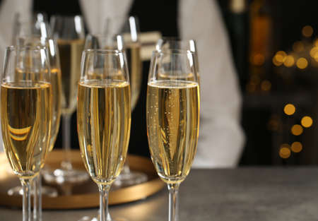 Glasses of champagne and waiter in restaurant, closeup. Space for text