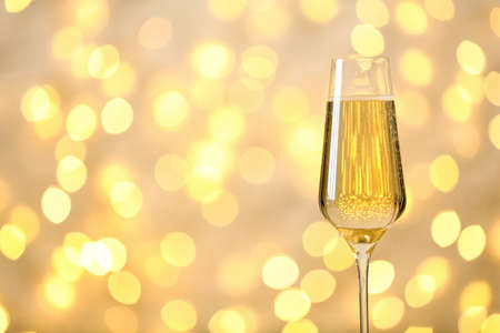 Glass of champagne against blurred lights. Space for text