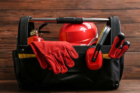 Black bag with construction tools on table against wooden background Stock Photo