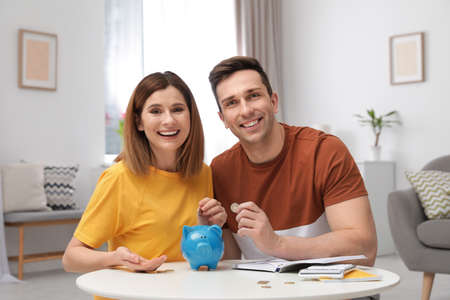 Couple putting coins into piggy bank at table in living room. Saving money