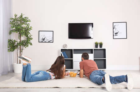 Young couple lying on carpet and watching TV at home Banco de Imagens