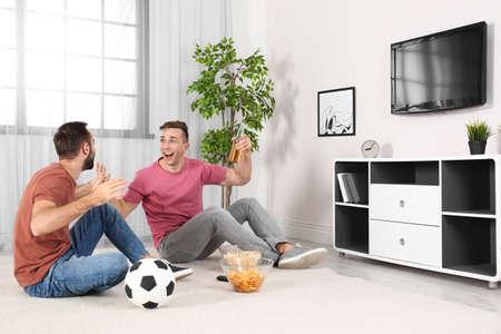 Hombres jóvenes viendo la televisión mientras están sentados en el suelo en casa. Canal deportivo Foto de archivo