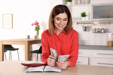 Smiling woman counting money at table indoors