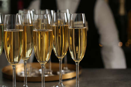 Glasses of champagne and waiter in restaurant, closeup