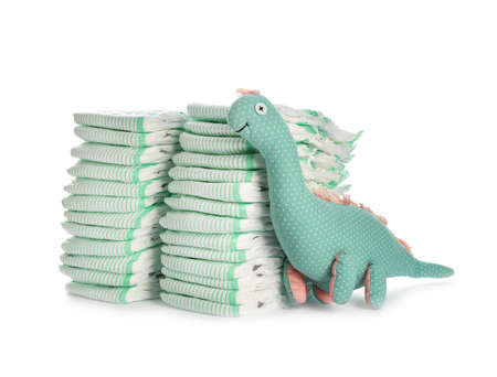 Disposable diapers and toy dinosaur on white background. Baby accessories