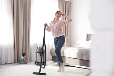 Happy woman having fun while cleaning bedroom Stock Photo