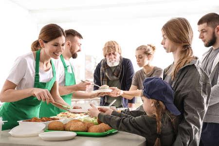 Volunteers giving food to poor people indoors Stock Photo