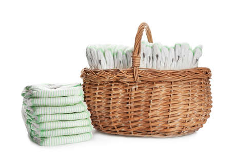 Wicker basket and disposable diapers on white background. Baby accessories