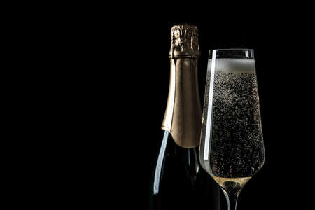 Bottle and glass of champagne on black background, space for text Banco de Imagens