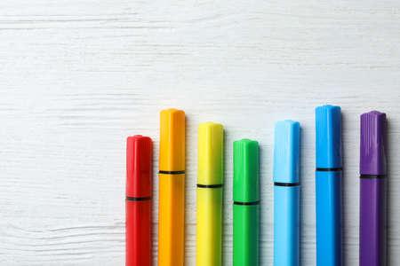 Composizione piatta con pennarelli colorati e spazio per il testo su fondo di legno bianco. Tavolozza arcobaleno