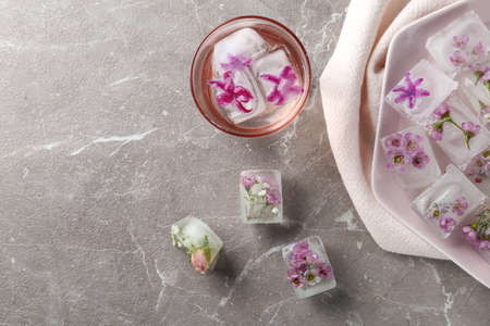 Flat lay composition with floral ice cubes on table. Space for text Imagens