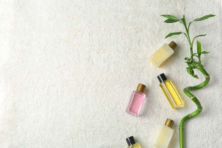Mini bottles with cosmetic products on towel, top view and space for text. Hotel amenities Stock Photo