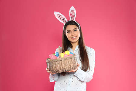 Beautiful woman in bunny ears headband holding basket with Easter eggs on color background
