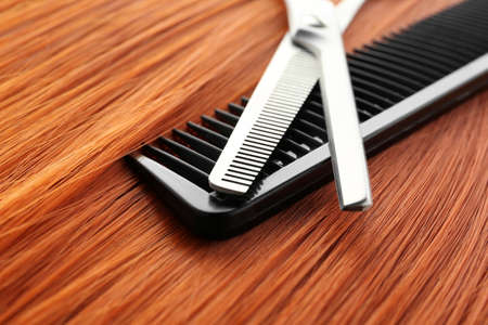 Thinning scissors and comb on red hair, closeup. Hairdresser service Stock Photo - 120964048