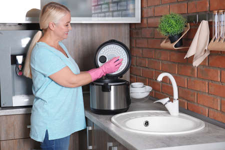 Mature woman cleaning modern multi cooker at kitchen counter