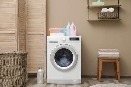 Machine à laver moderne près du mur de couleur à l'intérieur de la buanderie
