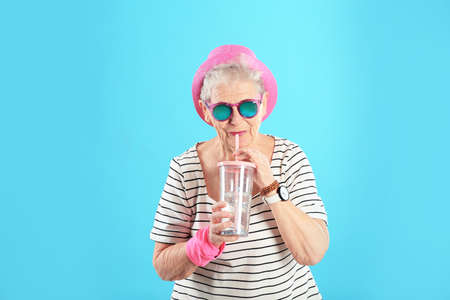 Portrait of cool grandmother with drink on color background