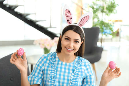 Beautiful woman in bunny ears headband holding Easter eggs at home