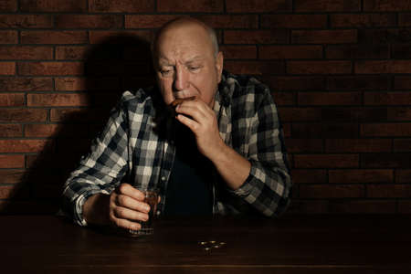 Poor senior man with bread and glass of water at table near brick wall Stock Photo