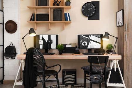 Stilvolles Arbeitsplatzinterieur mit Computern auf dem Tisch