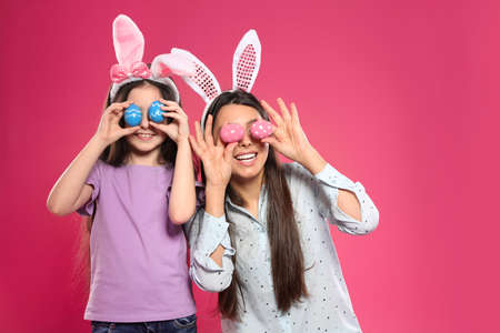Mother and daughter in bunny ears headbands holding Easter eggs near eyes on color background