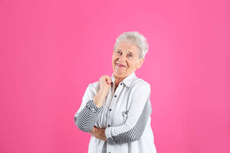 Portrait of grandmother in stylish clothes on color background